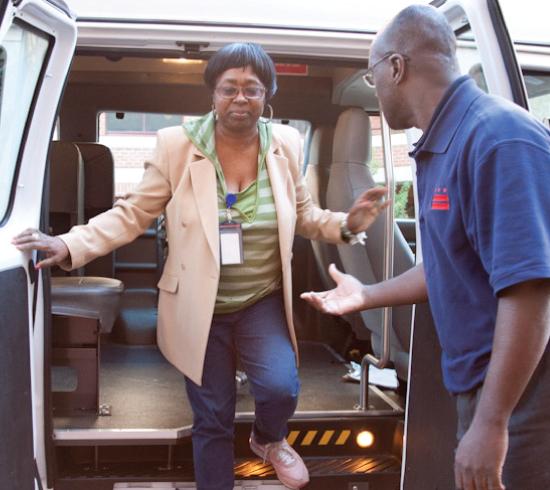 Driver helping passenger out of paratransit van