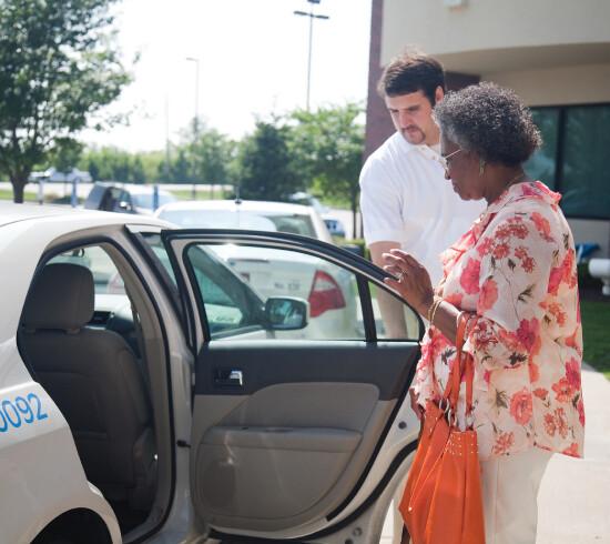 Driver holding car door open for passenger