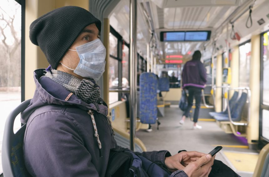 A mean wearing a face mask rides on a public transit train. SDoH like lack of transportation access can negatively affect health outcomes.