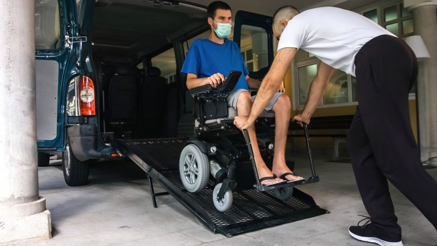 A driver helps a man who utilizes a wheelchair into his accessible vehicle. When patients use NEMT services to attend regular medical care instead of the ambulance to emergency services, emergency room diversion is successful.